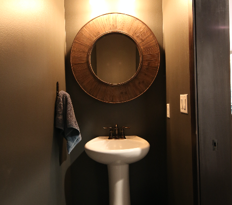 Dark Guest Bath with Round Wood Mirror Stebral Construction Home Builder Iowa City, Coralville, Solon, North Liberty
